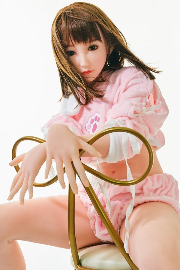 Kaddy 165 cm sex doll, posing on a chair in a bright pink pajama style outfit